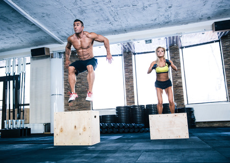 Group of man and woman jumping on fit box at gym