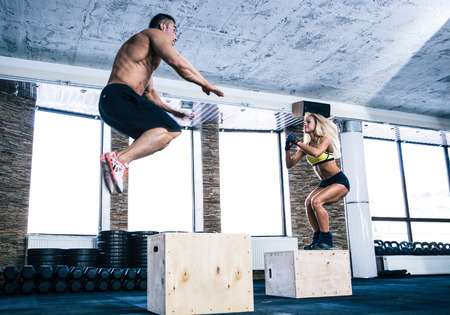 interval: Man and woman jumping on fit box at gym