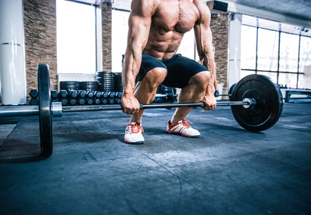 muskeltraining: Nahaufnahmeportrait eines muskulösen Mannes Training mit Langhantel auf Fitnessstudio