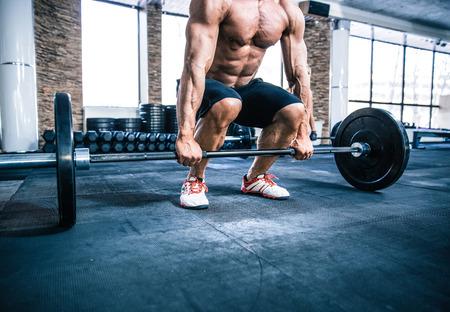 levantando pesas: Retrato del primer de un hombre de entrenamiento muscular con mancuerna en el gimnasio