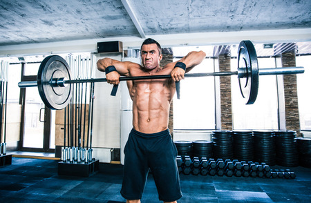 concetrated: Handsome fitness man lifting barbell at gym