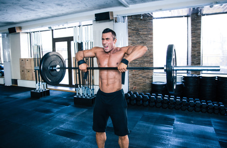 concetrated: Fit man lifting barbell at gym