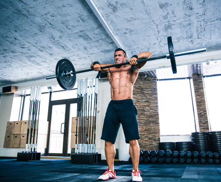 concetrated: Muscular man lifting barbell at gym