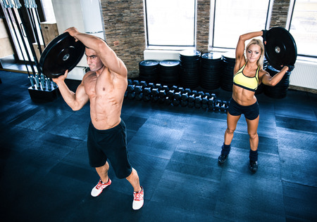 Muscular man and woman workout at crossfit gym photo