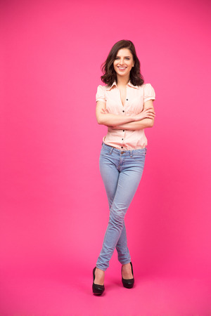 fold: Full length portrait of a happy woman with arms folded standing over pink background