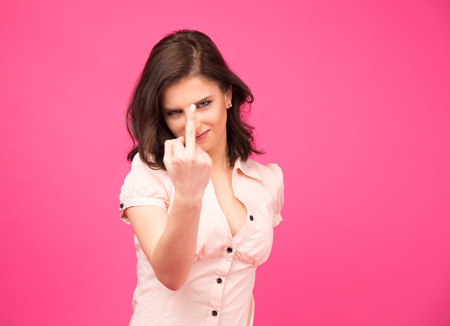 Beautiful woman showing middle finger over pink background. Provocation concept Stock Photo