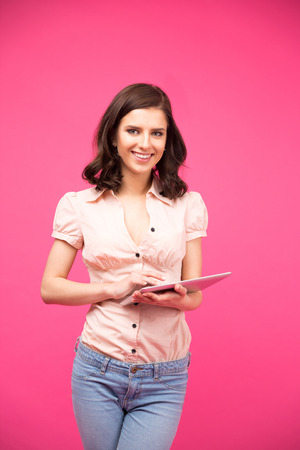 Smiling woman standing with tablet computer over pink background and looking at camera photo