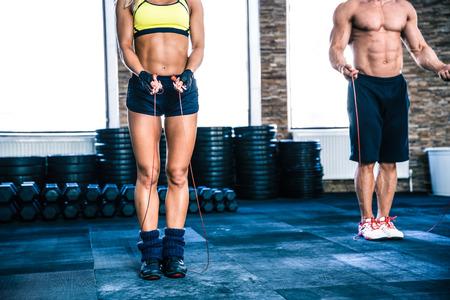 persona saltando: Hombre y mujer de entrenamiento con la cuerda de salto en el gimnasio de crossfit
