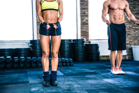 skipping: Man and woman workout with jumping rope at crossfit gym