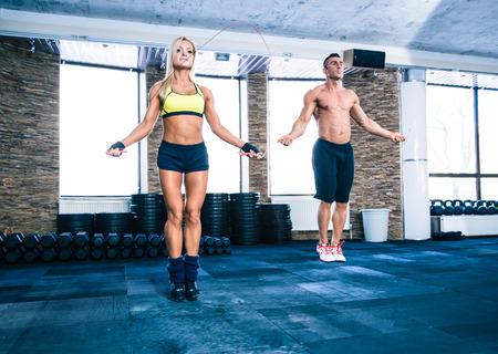 saltar la cuerda: Hombre musculoso y hermosa mujer de entrenamiento deportivo con saltar la cuerda en el gimnasio de crossfit