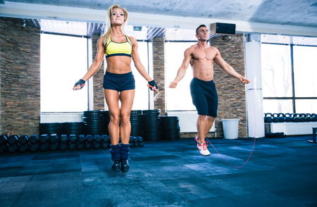 cardio fitness: Handsome muscular man and beautiful sporty woman workout with jumping rope in crossfit gym Stock Photo
