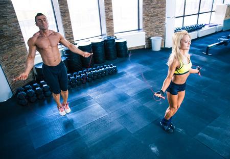 Fitness man en vrouw training met touwtjespringen in CrossFit sportschool
