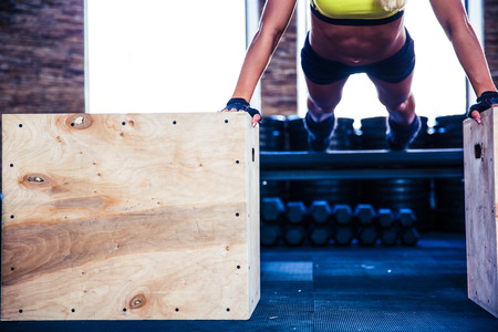 exercise equipment: Fit woman doing push ups on fit box at gym Stock Photo
