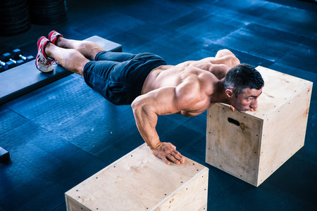 push: Muscular man doing push ups on fit box and bench at gym