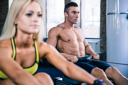 concetrated: Handsome man and beautiful woman doing exercises on training simulator in crossfit gym. Focus on man