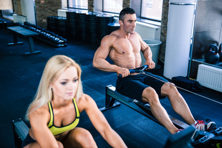 crossfit: Muscular man and sporty woman doing exercises on training simulator in crossfit gym. Focus on man