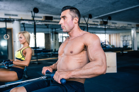 concetrated: Muscular man and sporty woman workout on training simulator in crossfit gym