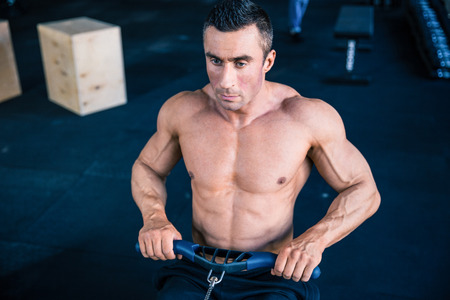 simulator: Handsome man working out on training simulator at crossfit gym