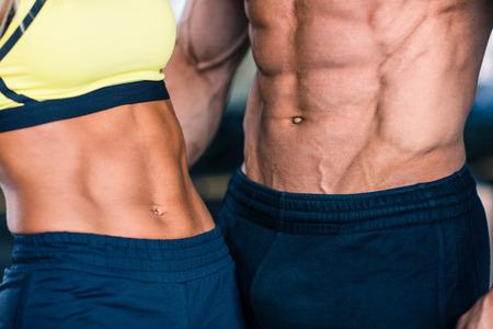 근육질 남자의 스포티 한 여자의 몸통의 근접 촬영 이미지 스톡 콘텐츠
