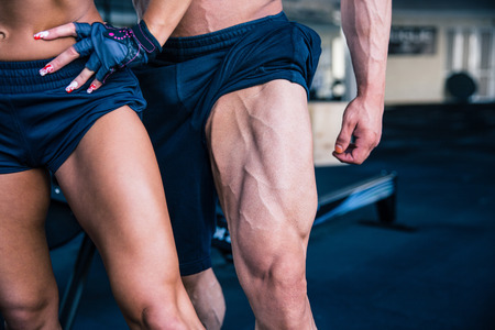 woman legs: Closeup image of a strong woman and muscular man posing at gym