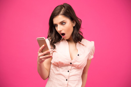 cellular phones: Surprised woman using smartphone over pink background. Wearing in shirt Stock Photo