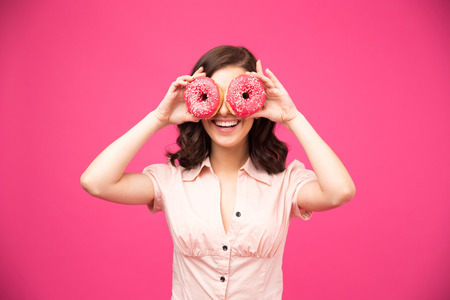 Woman covering her eyes with donut over pink donut Stock Photo