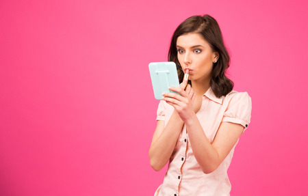 putting lipstick: Young woman holding mirror and putting lipstick on lips over pink background Stock Photo