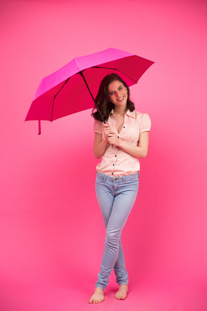 Happy woman standing with umbrella over pink background. Wearing in jeans and shirt. Barefoot. Looking at camera