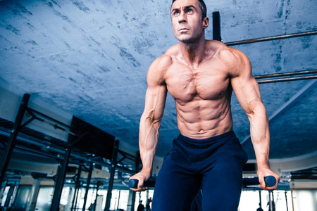 concetrated: Handsome muscular man workout on bars in crossfit gym