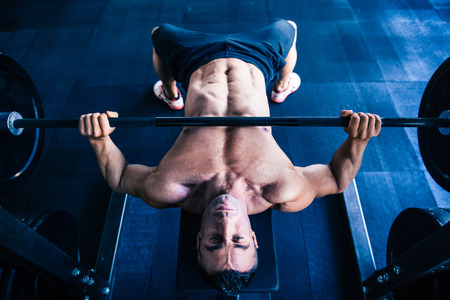 human chest: Muscular man workout with barbell on bench at gym