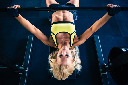 girl in sportswear: Fitness woman workout with barbell on bench in gym Stock Photo