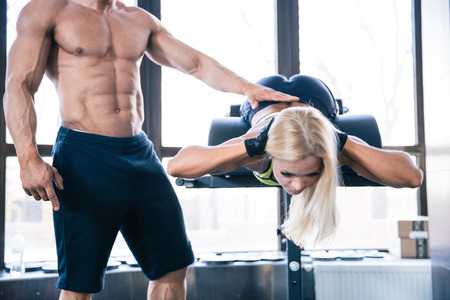 flexing: Woman flexing back muscles on bench with coach in gym