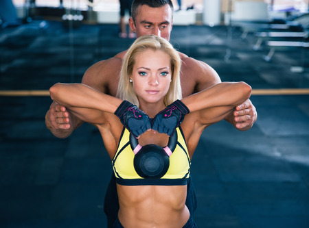 chest women: Woman workout with kettle ball and coach in gym