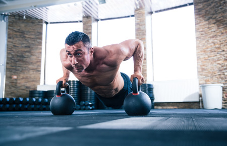 crossfit: Handsome muscular man doing push ups on kettle ball in crossfit gym