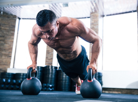 muscular: Guapos musculosos hombre haciendo flexiones en bola hervidor de agua en el gimnasio crossfit Foto de archivo