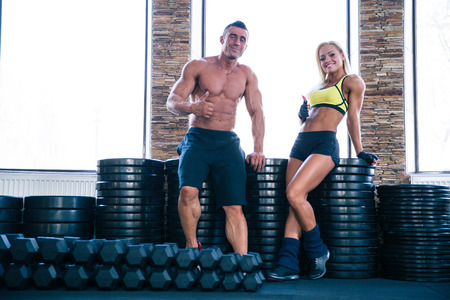 Happy sporty woman and muscular man showing thumb up in gym photo