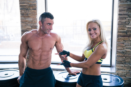 Beautiful happy woman showing on man`s press in gym