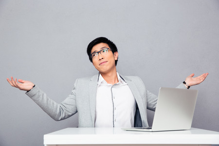 Businessman sitting at the table with laptop and shrugging over gray background