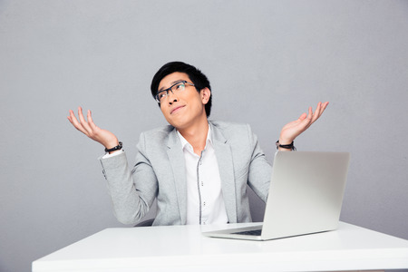 unknowing: Young businessman sitting at the table with laptop and shrugging over gray background. I dont know.