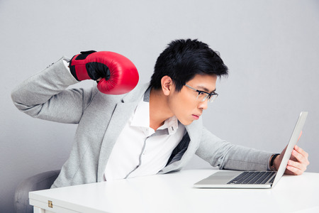 pugilist: Young businessman in boxing gloves and glasses sitting at the table and reading to hit laptop over gray background