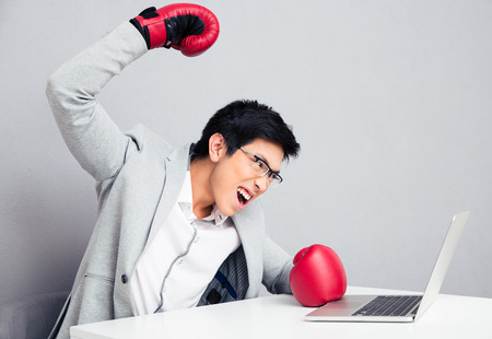 pugilist: Angry young businessman sitting at the table in boxing gloves. Ready to hit the laptop Stock Photo