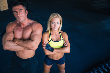 Group of a muscular man and fitness woman standing with arms folded in crossfit gym. Looking at camera