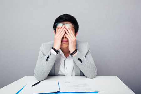 tired face: Young asian businessman sitting at the table and rubbing his eyes over gray background Stock Photo