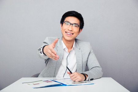Smiling asian businessman sitting at the table and stretching hand for handshake over gray background. Looking at camera photo