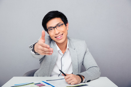 Happy young asian businessman sitting at the table stretching hand for handshake photo