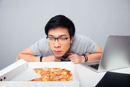 Young asian man sitting at the table and smelling pizza Imagens