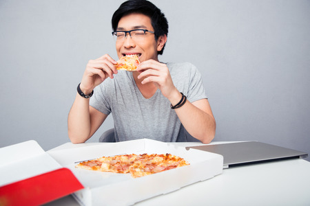 eating pizza: Young asian man eating pizza in office over gray background