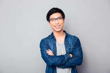 man  glasses: Portrait of a happy asian man with arms folded over gray background. Looking at camera