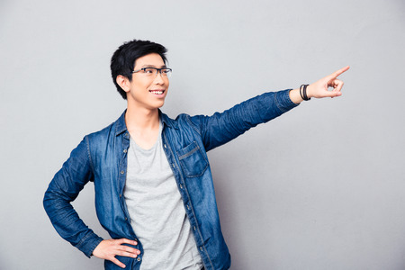 mockery: Happy asian man showing finger away over gray background Stock Photo