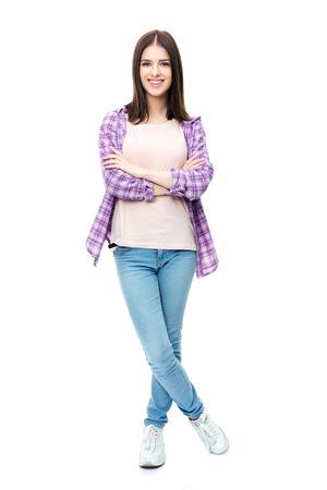 ホワイト バック グラウンドに立って腕組みとカメラ目線で笑顔のかわいい女子学生の完全な長さの肖像画